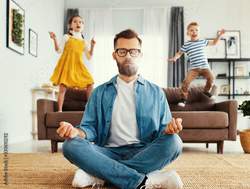 Father meditating in room with playful kids Canvas