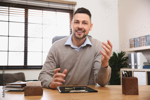 Man using video chat in office, view from web camera