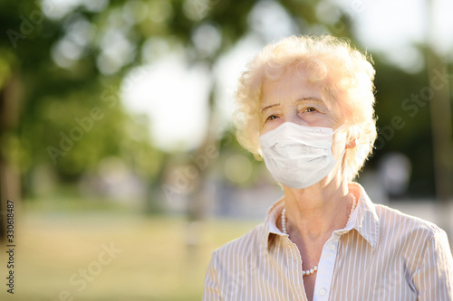 Fotomural Outdoors portrait senior woman wearing disposable medical face mask