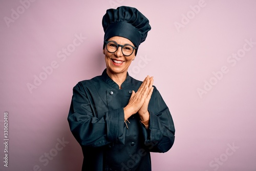 Photo Middle age brunette chef woman wearing cooker uniform and hat over isolated pink