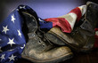 Closeup of old combat boots and an American flag.