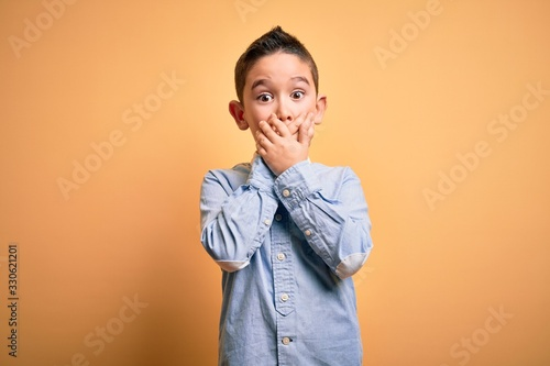 Fototapeta Young little boy kid wearing elegant shirt standing over yellow isolated background shocked covering mouth with hands for mistake. Secret concept. obraz