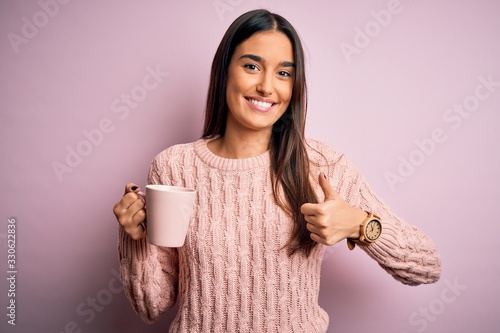 Fototapeta Young beautiful brunette woman drinking cup of coffee over isolated pink backgro