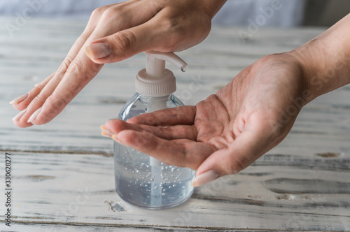 Obraz Young woman using hand sanitizer gel with liquid alcohol disinfectant for prevention of coronavirus and other pandemic and epidemic diseases - fototapety do salonu