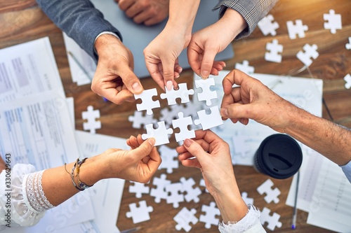 Canvastavla Group of business workers with hands together connecting pieces of puzzle at the