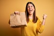 Leinwanddruck Bild - Young beautiful woman holding take away paper bag from delivery over yellow background screaming proud and celebrating victory and success very excited, cheering emotion