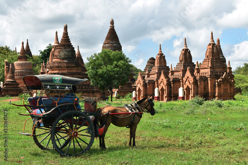 Horse drawn carriage tourists is driving along in front of the ancient temple of Bagan, Myanmar Wallpaper Mural