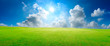 Green grass field and blue sky with white clouds,panoramic view.
