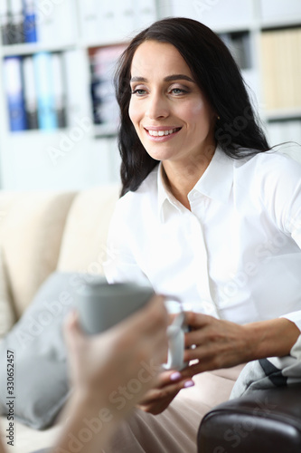 Woman is sitting in office with cup tea and talking Canvas Print