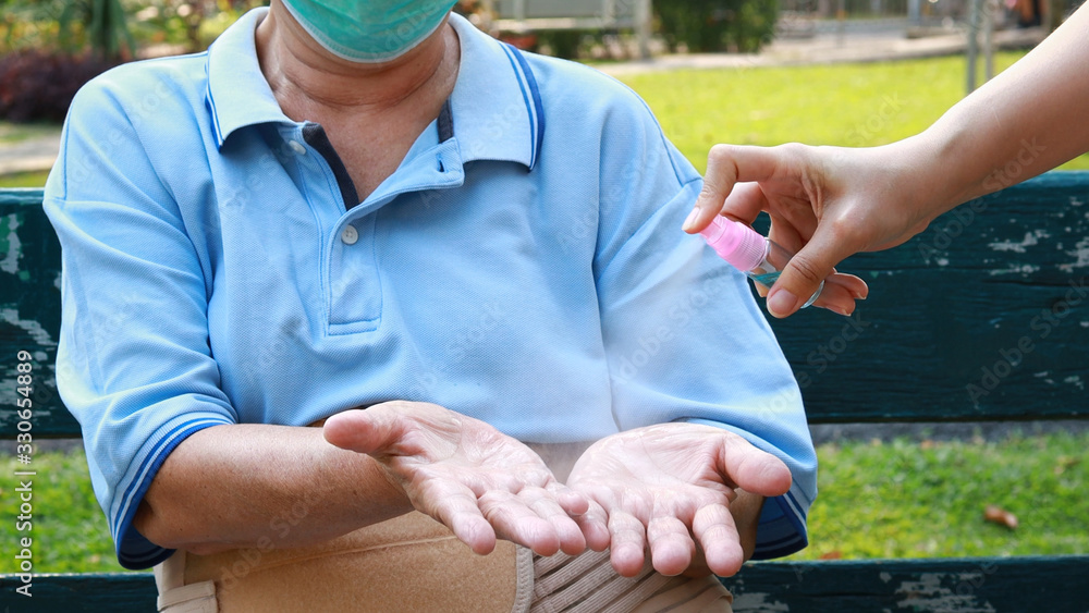 Fototapeta Alcohol spraying disinfection concept,caregiver woman is spraying alcohol on palms or hands of senior people,prevent infection of Covid-19 virus,pandemic of Coronavirus,cleaning,wash hands frequently