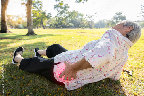 Obraz Asian elderly people have an accident because of her walking exercise alone,slipped and fell to the floor,senior woman lying on the ground,touch her painful hips,waist or buttosks after falling down - fototapety do salonu