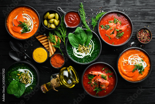 Fototapeta Set of colored soups. Spinach soup, tomato cream soup and carrot puree soup. Healthy food. On a black stone background. obraz