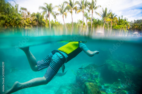 Underwater photo of Child snorkeling at a tropical resort Canvas Print