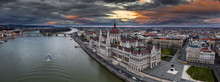 Budapest, Hungary - Aerial Panoramic Drone View Of The Beautiful Hungarian Parliament Building With Margaret Birdge And Island, Yellow Tram, Sightseeing Boat And A Dramatic Golden Sky At Background