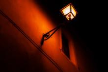 Vecchia Lampada Elettrica Che Illumina Un Muro Con Finestra In Centro Storico Di Città Italiana. Fotografia Notturna.