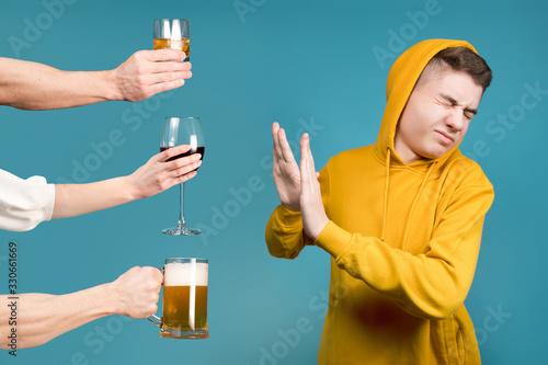 Fotografija Teenager in a yellow sweatshirt refuses different types of alcohol