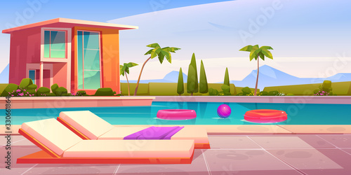 Fototapeta House and swimming pool with deck chairs on poolside and balls in water. Vector cartoon summer landscape with villa, basin on lawn, palms and mountains on background obraz