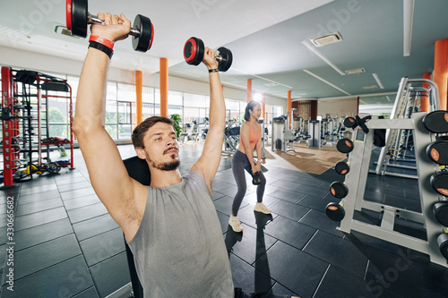 Obraz Handsome fit young man sitting on gym bench and lifting dumbbells , young woman standing near by and doing squats with small kettlebell - fototapety do salonu