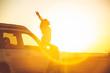 woman stop at roadside to enjoy sunset. sitting on car hood