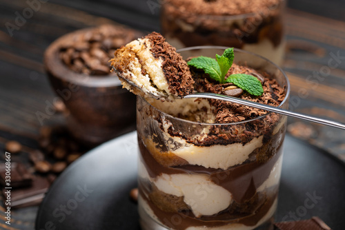 Leinwand Poster Classic tiramisu dessert in a glass cup on wooden background