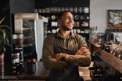 Young afro-american small coffee shop owner standing behind counter wearing apro Canvas Print