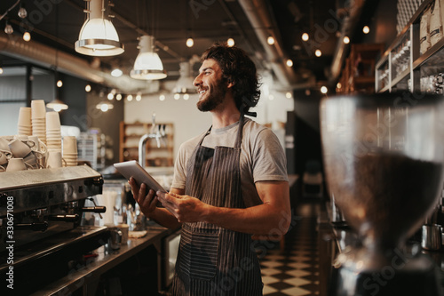 Fotomural Handsome caucasian man in coffee shop laughing while holding digital tablet in h