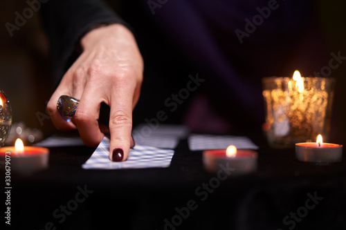 Close-up of fortune teller divining on cards sitting at table with burning candl Canvas Print
