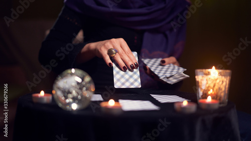 Close-up of woman fortuneteller hand with cards while sitting at table with cand Canvas Print