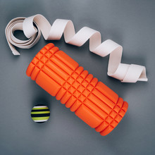 Set Of Green Fascia Release Ball, Orange Bumpy Foam Massage Roller For Trigger Points And Belt Over Grey Background.
