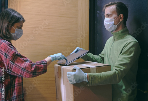 Obraz Courier in protective mask delivers parcel, customer in medical gloves signs on tablet. Delivery service under quarantine, disease outbreak, coronavirus covid-19 pandemic conditions. - fototapety do salonu