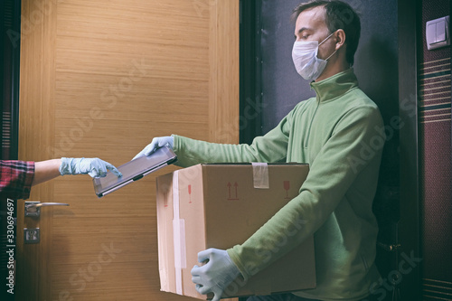 Obraz Courier in protective mask delivers parcel to client, client in medical gloves signs on tablet. Delivery service under quarantine, disease outbreak, coronavirus covid-19 pandemic conditions. - fototapety do salonu
