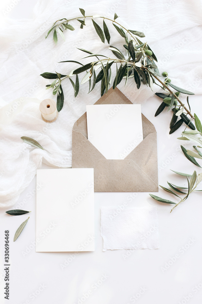 Fototapeta Summer wedding stationery mock-up scene. Blank greeting cards, envelopes, silver plate with olive branch and and silk ribbon. White table background in sunlight, shadows. Flat lay, top view, vertical.