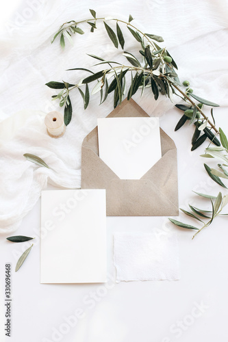 Fototapeta Summer wedding stationery mock-up scene. Blank greeting cards, envelopes, silver plate with olive branch and and silk ribbon. White table background in sunlight, shadows. Flat lay, top view, vertical. obraz
