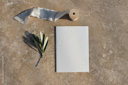 Fototapeta Summer wedding stationery mock-up scene. Blank greeting card, invitation with green olive branch and silk ribbon. Elegant golden marble background in sunlight, shadows. Flat lay, top view. obraz