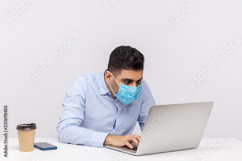 Fényképezés Flu-sick workaholic office employee in hygienic mask working on laptop, using protect filter against contagious disease coronavirus, looking crazy about his job in spite epidemic