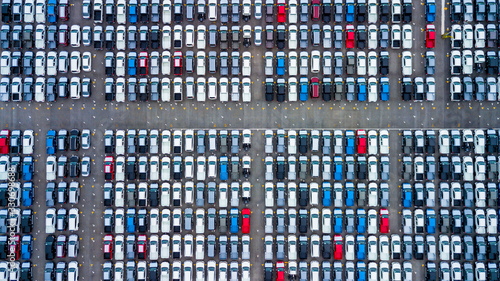Fototapeta Aerial view new cars parking for sale stock lot row, New cars dealer inventory import export business commercial global, Automobile and automotive industry distribution logistic transport worldwide. obraz