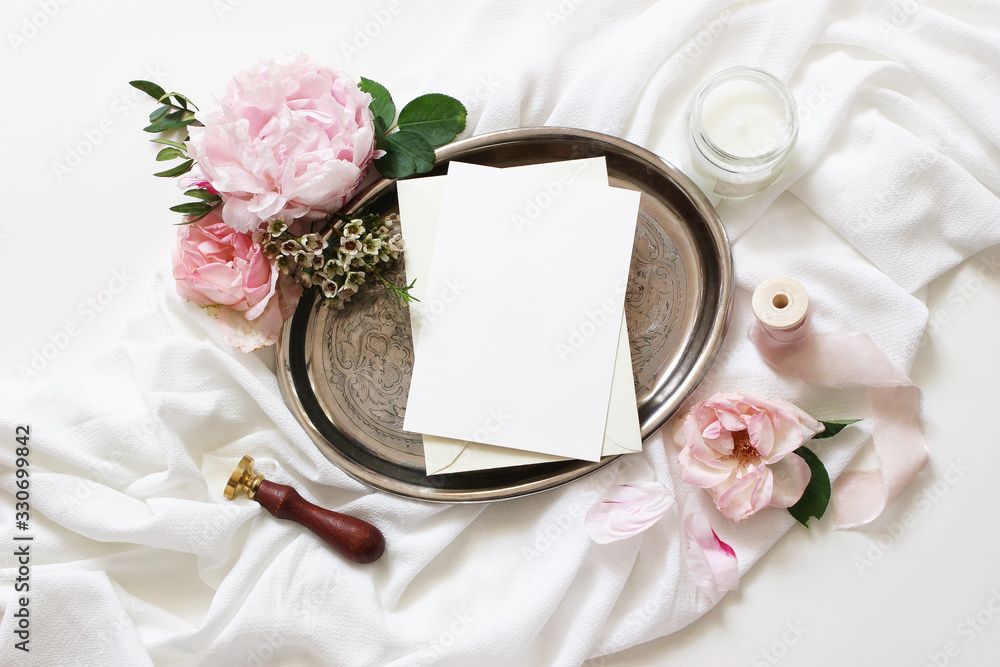 Fototapeta Feminine wedding, birthday mock-up scene. Blank paper greeting cards, candle, pink roses, silk ribbons, peony flowers on silver plate, White table background. Light, shadow play. Flat lay, top view