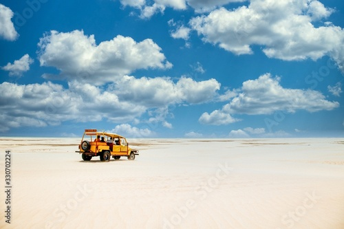 Yellow truck riding on the sandy ground under the cloudy blue sky