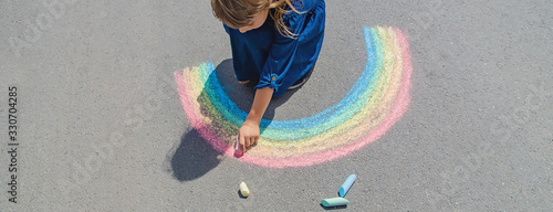 Obraz child draws with chalk on the pavement. Selective focus. - fototapety do salonu