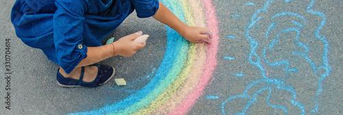 Fototapeta child draws with chalk on the pavement. Selective focus. obraz