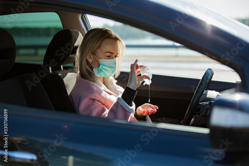 Obraz Woman in protective mask sitting in a car on road, using hand sanitizer. Safe traveling. - fototapety do salonu