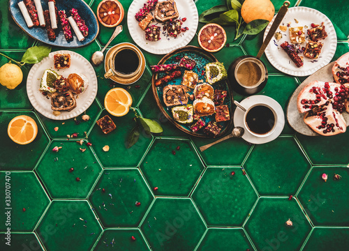 Fototapeta Flat-lay of variety of Turkish traditional lokum sweet delight with Turkish coffee in cups and fresh fruits over green Moroccan tile table, top view, copy space. Middle East typical dessert food obraz