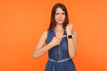 Worried Brunette Woman In Denim Dress Being Punctual, Looking Anxious And Impatient About Late Hour, Delay Or Deadline, Pointing To Wristwatch, Showing Clock. Studio Shot Isolated On Orange Background