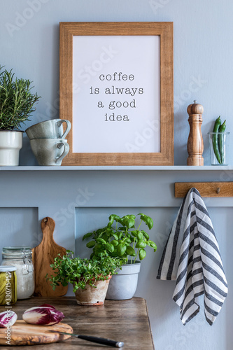 Obraz Interior design of kitchen space with mock up photo frame, wooden table, herbs, vegetables, food and kitchen accessories in modern home decor. - fototapety do salonu