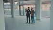 Man and real estate agent showing new apartment empty building look around use laptop realtor business caucasian rent consulting house home property slow motion
