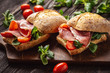 Jamon sandwiches with tomatoes, on wooden board.