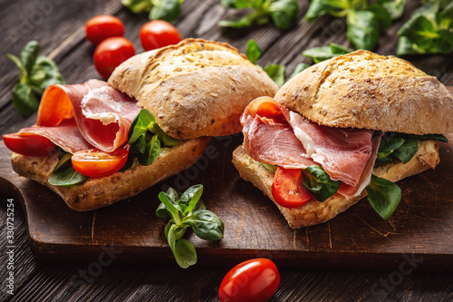 Fototapeta Jamon sandwiches with tomatoes, on wooden board. obraz