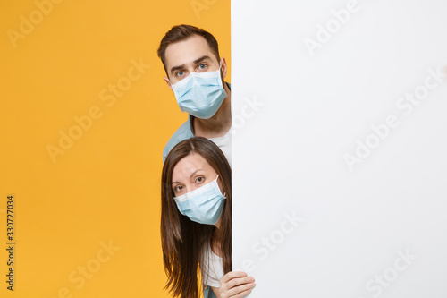 obraz PCV People in sterile face masks hold big white empty blank billboard isolated on yellow background studio. Epidemic rapidly spreading coronavirus 2019-ncov medicine flu virus ill sick treatment concept.