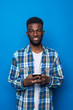 canvas print picture - Chatting with you. Portrait of young african man using mobile phone and smiling isolated on blue background