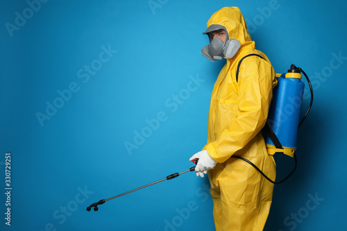 Man wearing protective suit with insecticide sprayer on blue background, space for text Fototapet